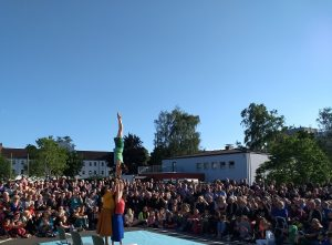 three women perform an acrobalance trick in front of a large audience.