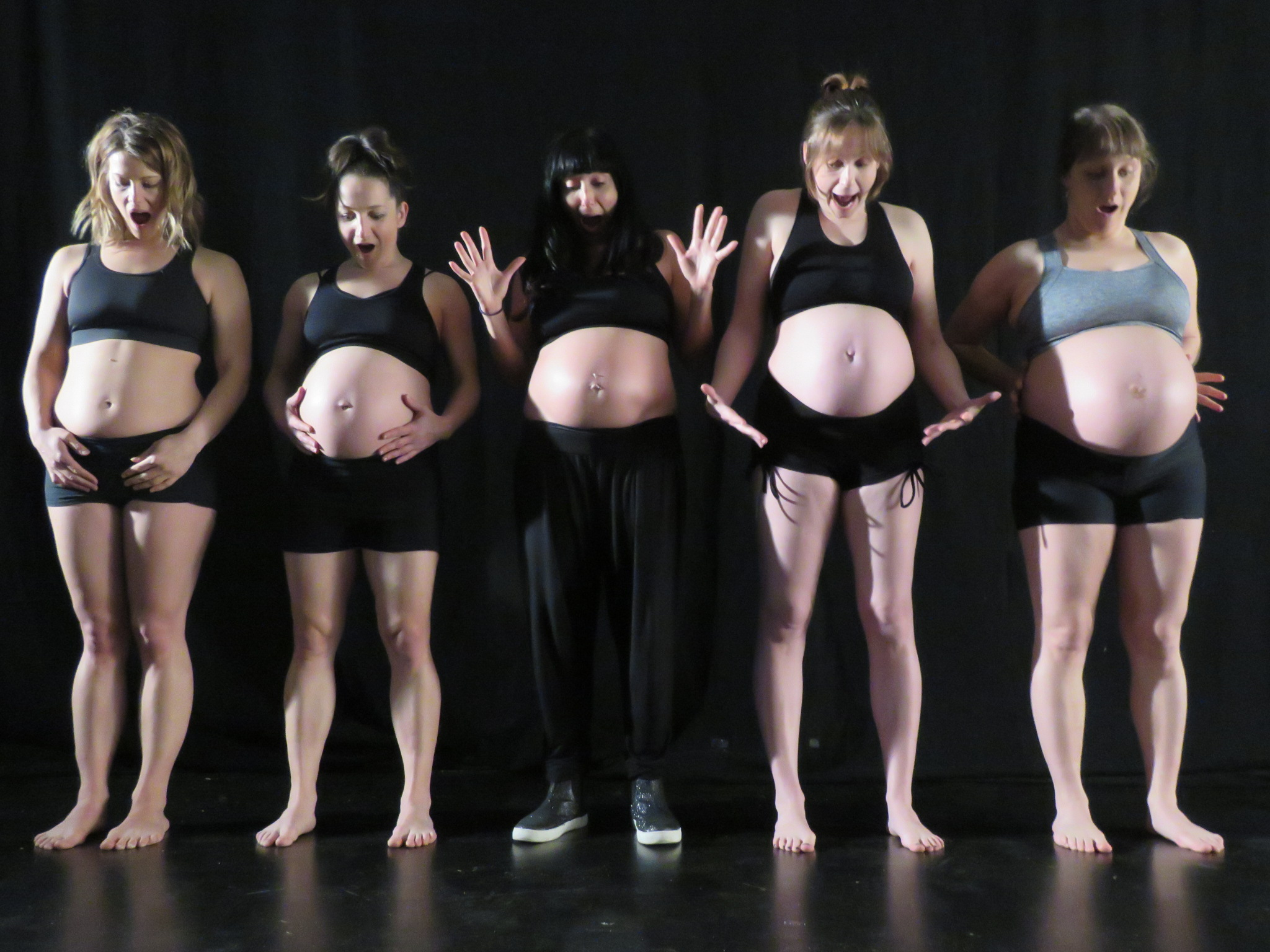 Five pregnant women standing in a line, looking down at their bumps in suprise, as if they have only just noticed they are pregnant.