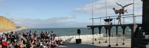 A large outdoor audience looking onto a raised stage with 3 acrobats performing on it with a baby crib on the stage with them. In the background is the English Channel on a sunny day.
