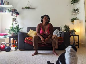 A mixed race woman in her early twenties sitting on her sofa and looks straight in the camera, she wears beige trousers and a bright pink bikini top, She has a cool and unimpressed facial expression with her elbows resting on her knees. In the background are a variety of potted plants, kettlebells, books and glass bottles. A white and black spotted cat sits looking into the camera in the right hand corner.