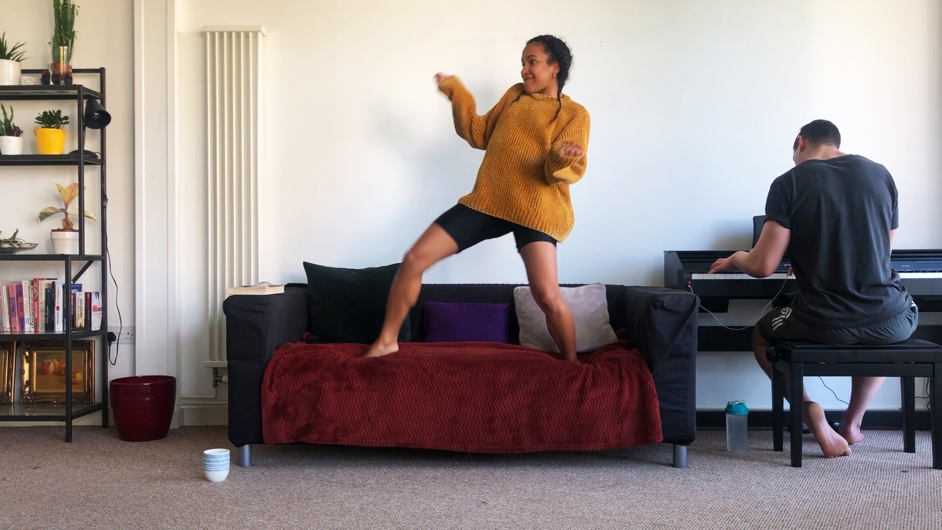 A mixed race woman her early thirties, in an ochre loose knit jumper and black shorts dancing on her black couch and a burgundy throw rug couch.