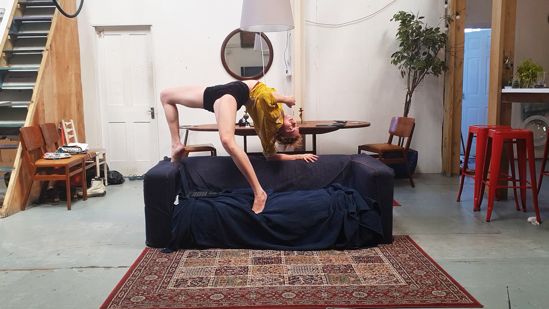 A white woman in her early twenties in a yellow shirt and black shorts is doing a one-handed bridge on her navy blue couch. In front of the couch is a mauve Persian-style rug.