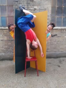a woman doing a handstand on a chair with two women l=behind her holding up wide planks and looking at the first woman from behind the prop walls.