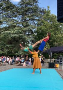 Three women in colourful costumes perform and acrobalance trick front of an outdoor audience