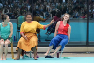 three women sitting on chairs. One of them is toppling to the side after being pushed by the woman sitting next to her. In the background is a reflects a large outdoor audience.