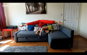 A woman in bright red trousers rolling in a headstand on blueish grey sofa her sofa doing the splits. She is in her twenties and is of East Asian heritage.