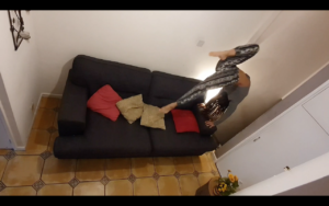 A young woman landing her feet from a handstand onto her dark grey sofa with ochre and red throw pillows on it.