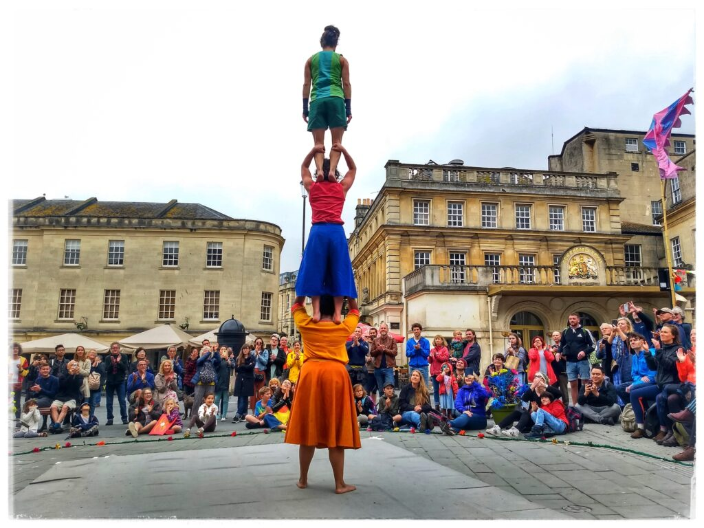 3 women standing on each others' shoulders in front of an outdoor audience