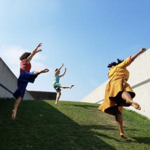 three women mid-jump on a grassy slope.