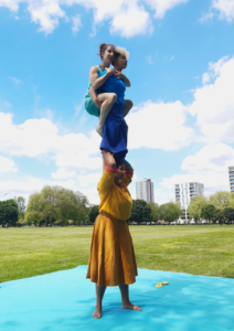 3 acrobats perform an acrobalance trick. 2 women on the shoulders of a third woman