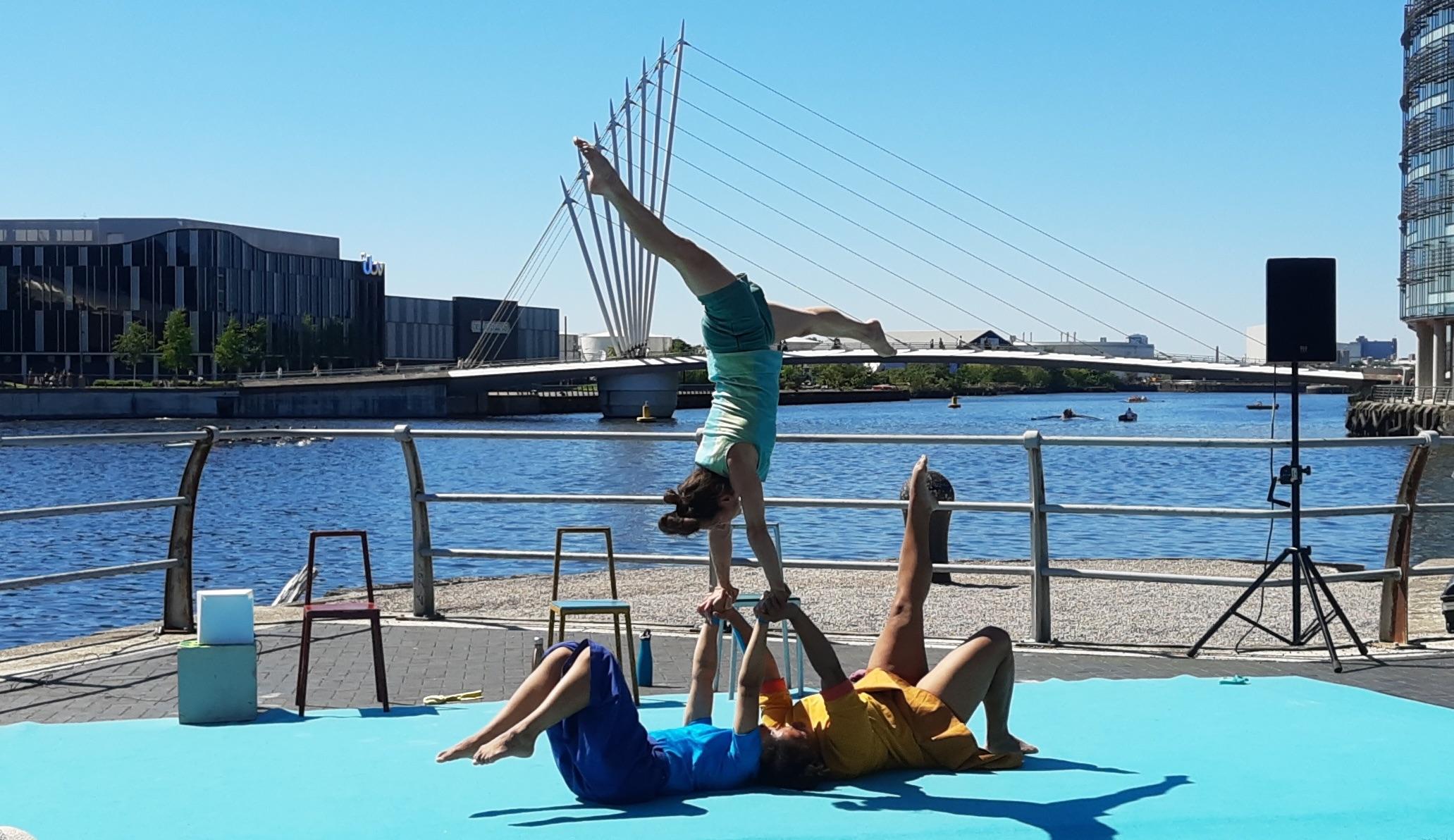 3 acrobats perform an acrobalance trick.