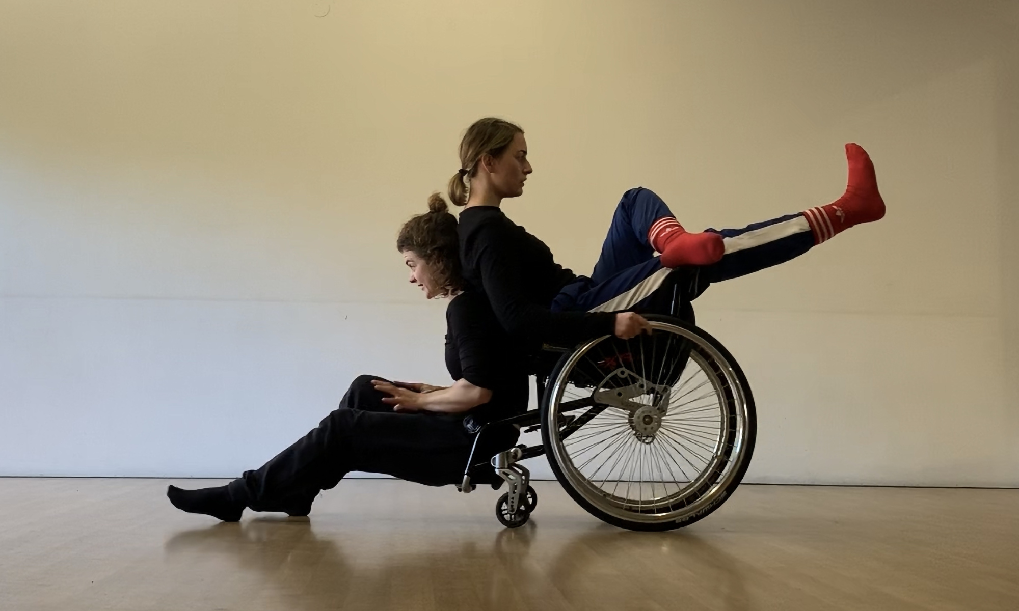 two women back to back, one of them is a wheel chair user.